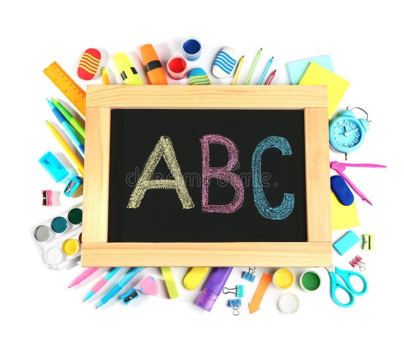 Klein bord met brieven ABC en verschillende schoolkantoorbehoeften op witte achtergrond royalty-vrije stock foto