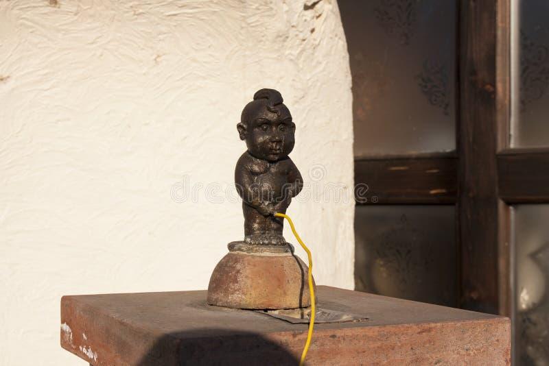 Klein bronsstandbeeld van beroemde Mannekene Pis, het iconische standbeeld van in de foto van Uzhgorod de Oekraïne - 1 April, 201 stock foto