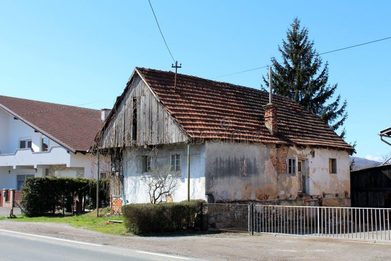 Klein die dilapidated familiehuis van hout en beton wordt gemaakt door eigenaars met gebarsten voorgevel wordt verlaten en gedeel royalty-vrije stock fotografie