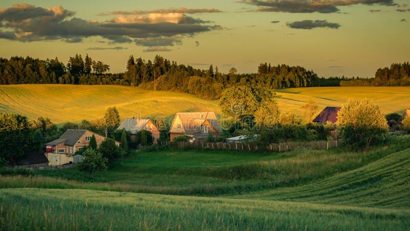klein dorp in het midden van een heuvelig landbouwgebied in het warme licht van zonsondergang royalty-vrije stock foto's