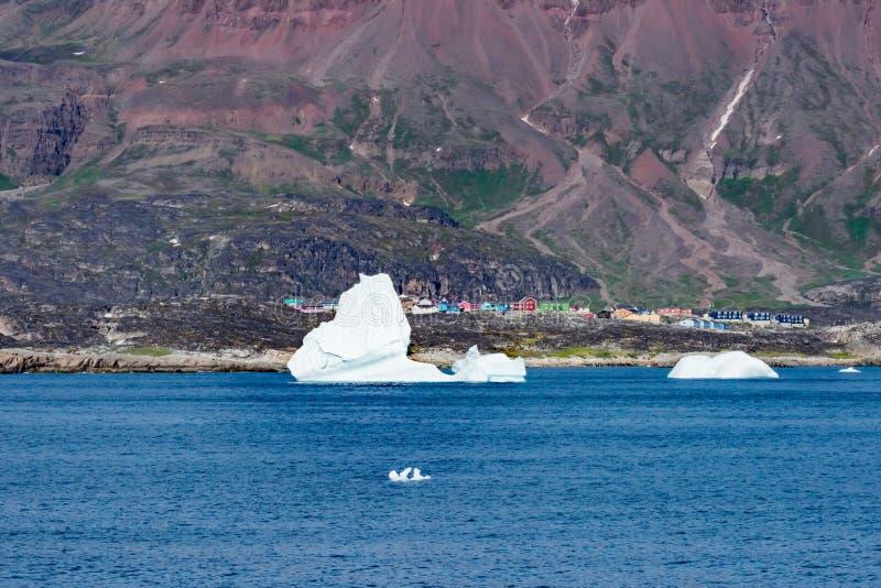 Klein dorp met kleurrijke blokhuizen en ijsberg vooraan in de rug van verder op Noordpooloceaan dichtbij Qeqertarsuaq, Groenland royalty-vrije stock foto's