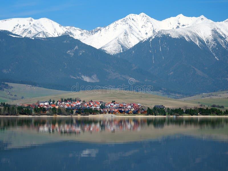 Klein dorp onder reusachtige bergen royalty-vrije stock afbeeldingen