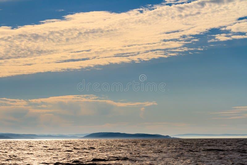Klein eiland in de Barentsz Zee op de zonsondergang Noordpooloceaan, Kola Peninsula, Rusland stock foto