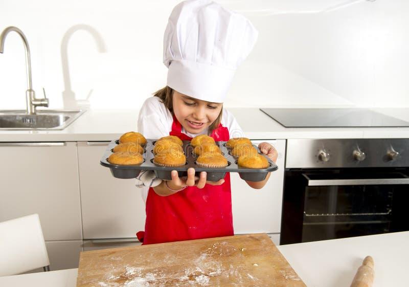 Klein en leuk meisje alleen in kokhoed en schort die en dienblad met muffins gelukkig glimlachen voorstellen tonen royalty-vrije stock afbeelding