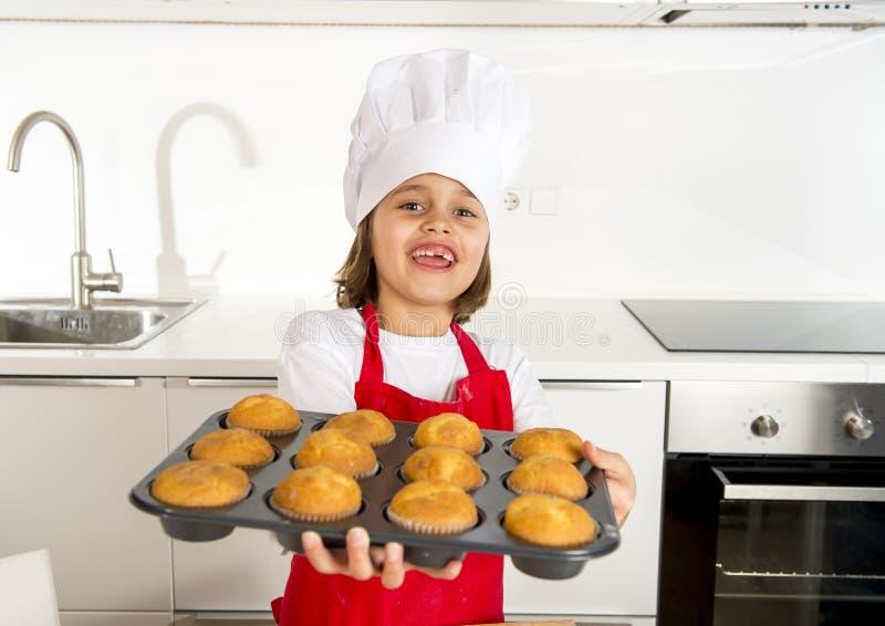 Klein en leuk meisje alleen in kokhoed en schort die en dienblad met muffins gelukkig glimlachen voorstellen tonen stock foto
