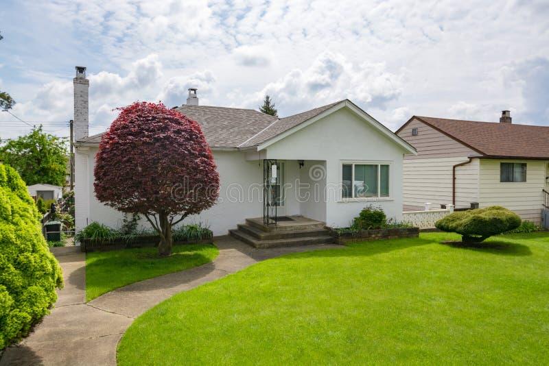 Klein familiehuis met groen gazon en decoratieve boom vooraan stock afbeeldingen