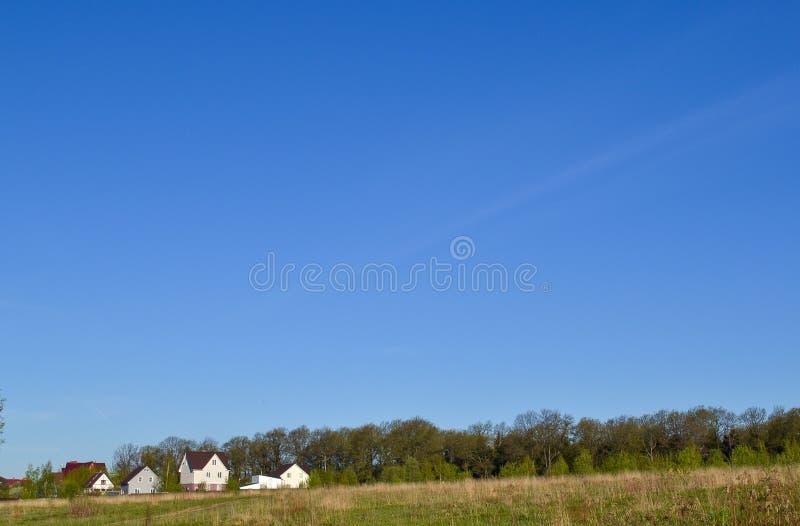 Klein familiehuis op groen gebied met blauwe hemel royalty-vrije stock foto's