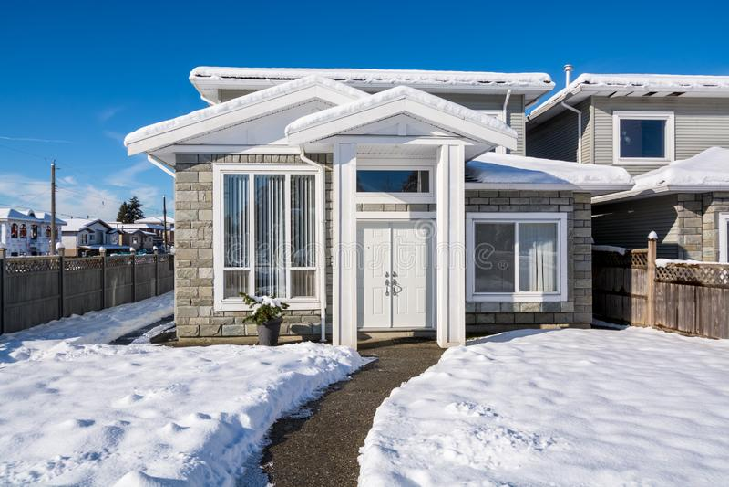 Klein familiehuis in sneeuw bij de wintertijd in Canada stock afbeeldingen