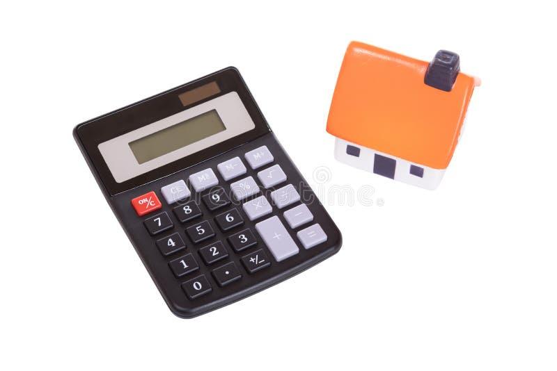 Klein geïsoleerd calculator en stuk speelgoed huis op wit royalty-vrije stock foto
