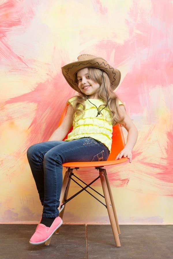 Klein gelukkig babymeisje in cowboyhoed op oranje stoel stock foto