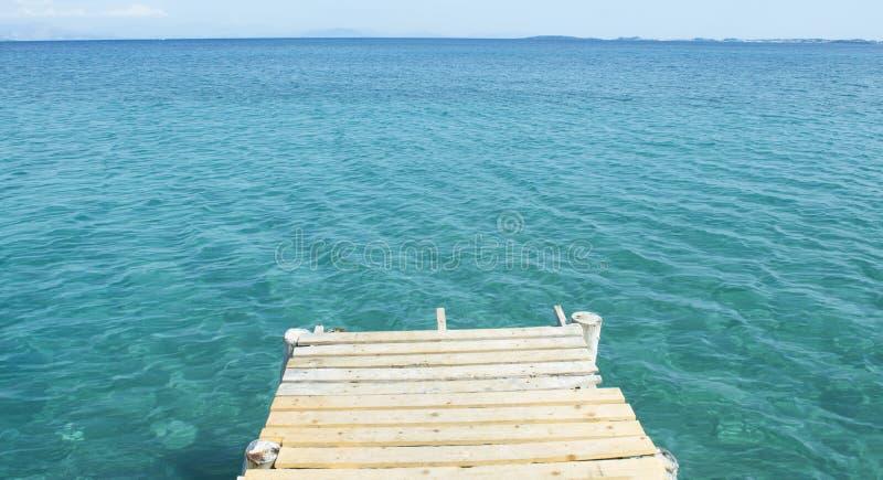 Klein houten dok en blauwe overzees stock foto