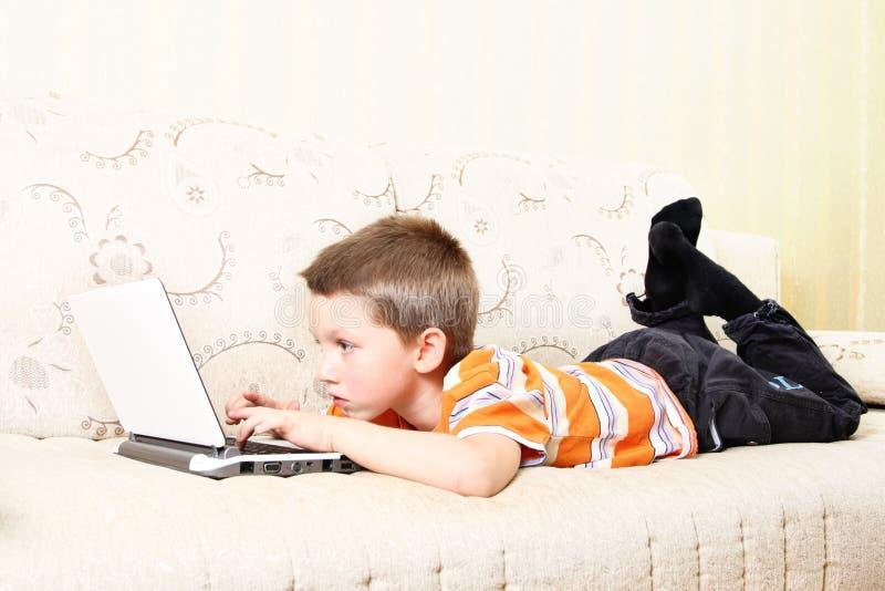 Klein jong geitje met laptop stock afbeeldingen