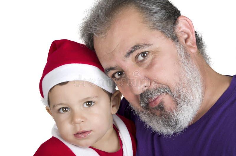 Klein jong geitje in Santa Claus-kleren met zijn grootvader royalty-vrije stock fotografie