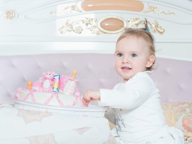 Klein Kaukasisch kindmeisje op gelukkige verjaardag met cake thuis stock afbeelding