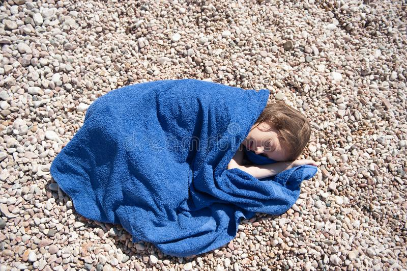 Klein Kaukasisch meisje die op strand die blauwe handdoek wraping in de hete dag van de de zomermiddag liggen stock foto's