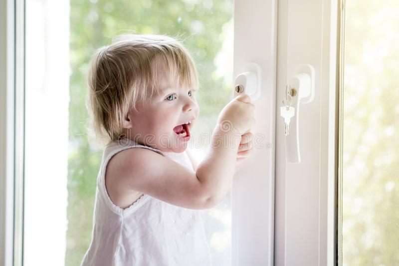 Klein kind dichtbij venster slot op handvat van venster Kind ` s safet stock afbeelding