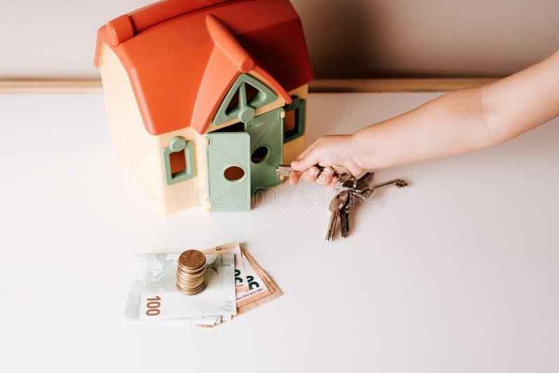 klein kind die, met in hand sleutels, de deur van het stuk speelgoed huis proberen te openen stock foto's