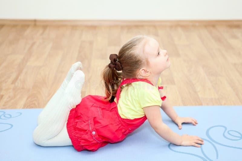 Klein kind die recreatieve gymnastiek op mat maken royalty-vrije stock foto