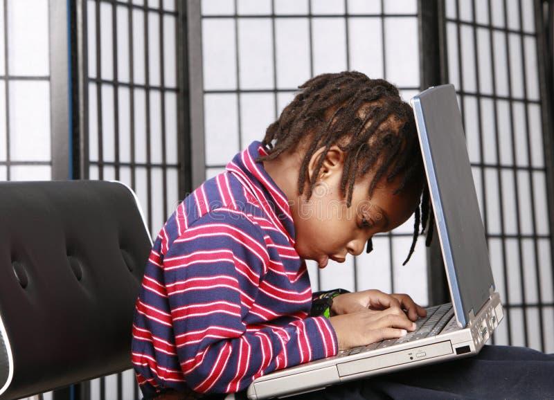 Klein kind met een computer stock afbeeldingen