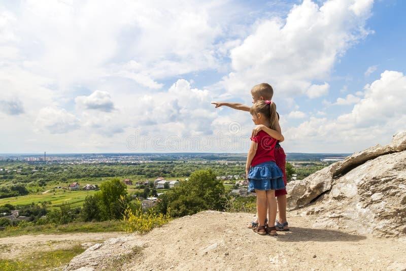 Klein kinderenjongen en meisje die zich op bergrots en looki bevinden stock foto's
