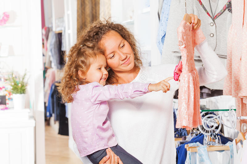Klein leuk meisje met haar moeder die kleding kiezen stock fotografie