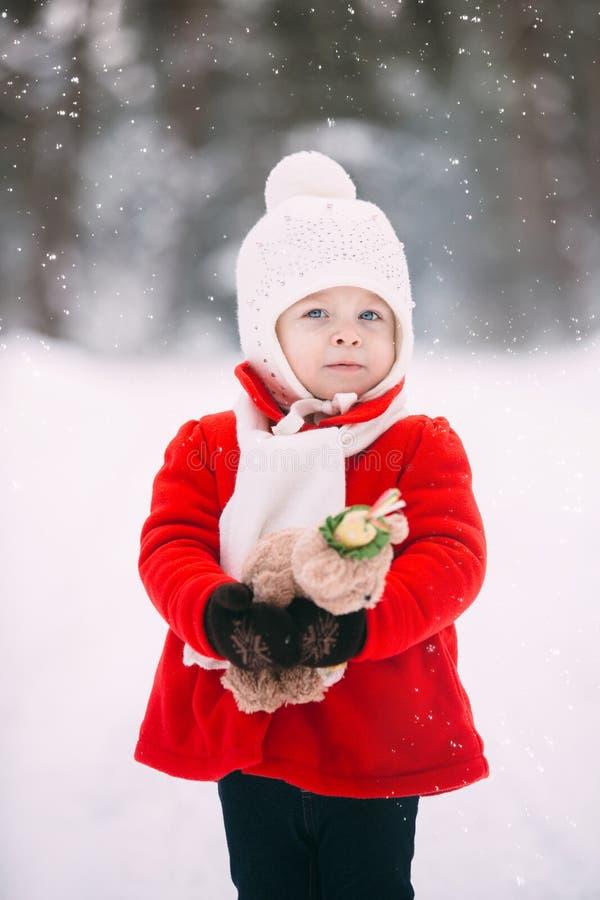 Klein Mädchen in rotem Mantel mit einem Teddybären, der am Wintertag Spaß hat Schneemobil lizenzfreies stockbild
