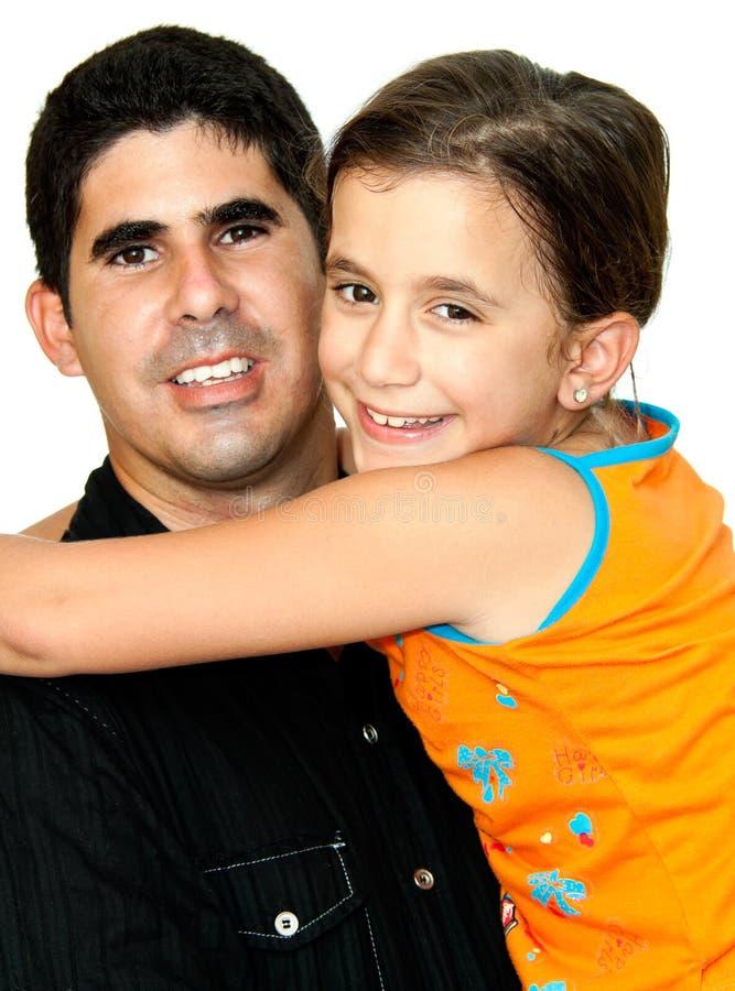 Klein meisje dat een jonge Latijnse mens koestert stock foto