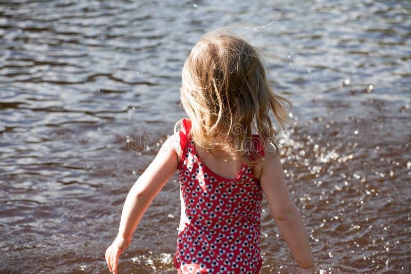 Klein meisje dat staat voor het wateroppervlak van het meer stock afbeeldingen