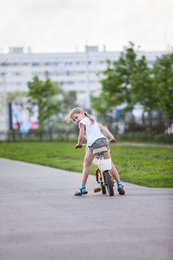 Klein meisje dat terug wanneer berijdende fiets kijkt stock afbeeldingen