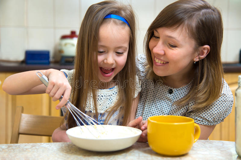 Klein meisje die het deeg voor pannekoeken gaan slaan royalty-vrije stock foto's