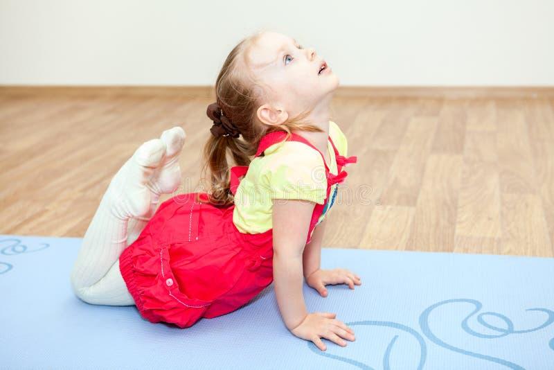 Klein meisje die yoga maken op mat in gymnastiek stellen stock afbeeldingen