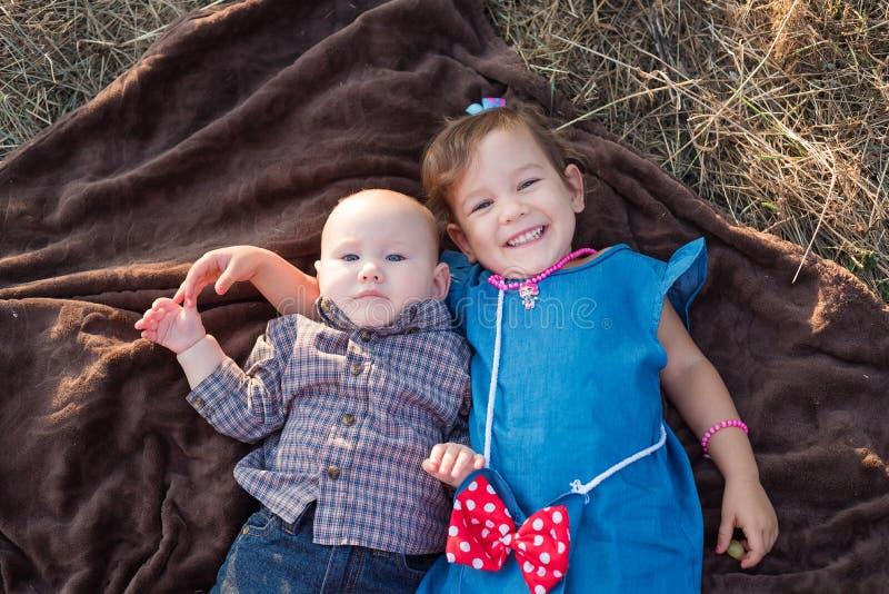 Klein meisje en jongen die elkaar omhelzen op herfstdag broertje en zusje knuffelen royalty-vrije stock foto's