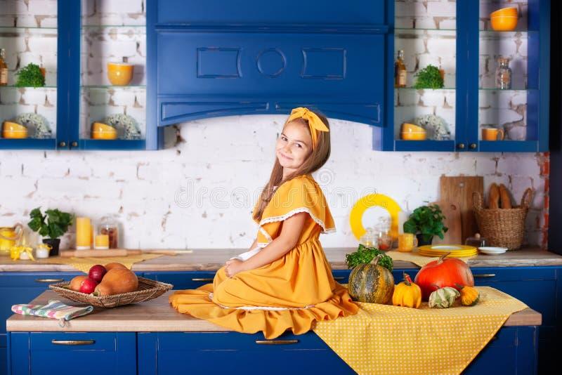 Klein meisje in gele jurk in herfstdecor met pompoenen in de keuken, Halloween-vakantie Oogst Gezonde voeding, vegetarisch royalty-vrije stock fotografie