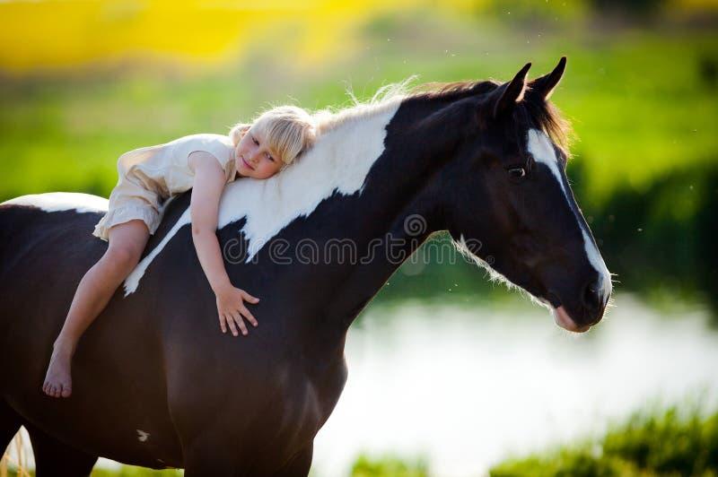 Klein meisje het berijden paard stock afbeelding