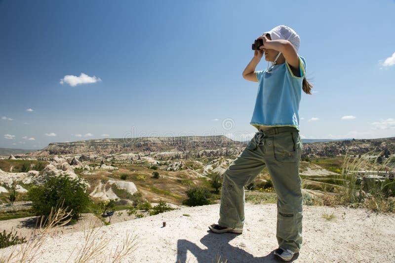 Klein meisje met binoculair in bergen stock fotografie