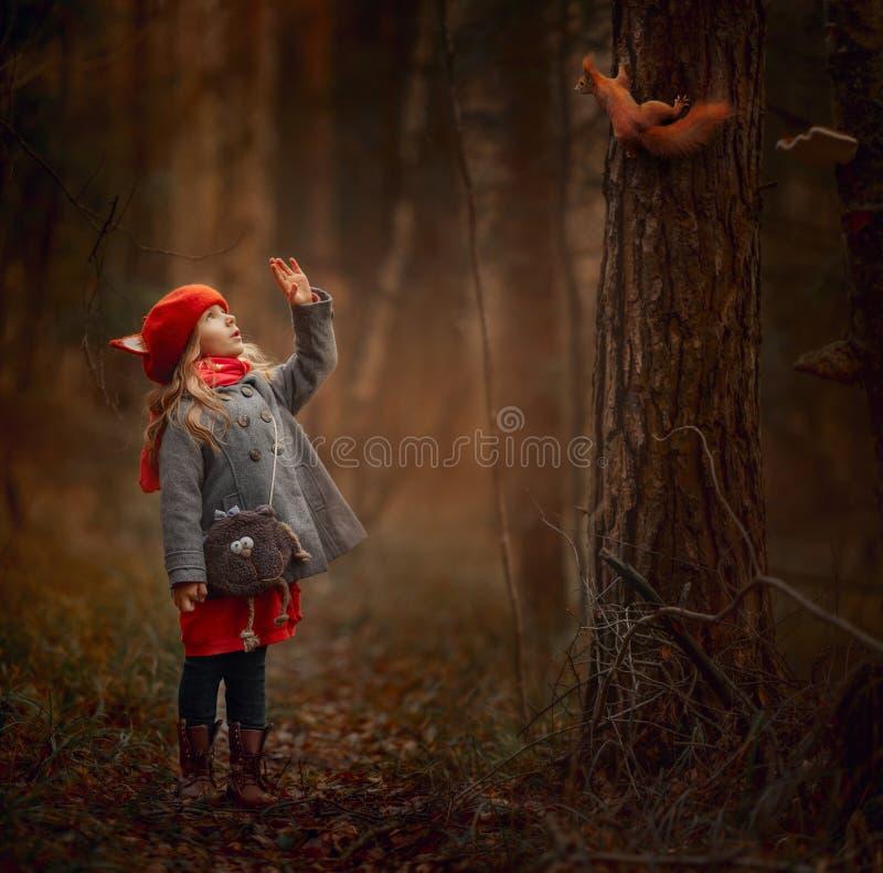 Klein meisje met eekhoorn in een herfstbos stock afbeelding