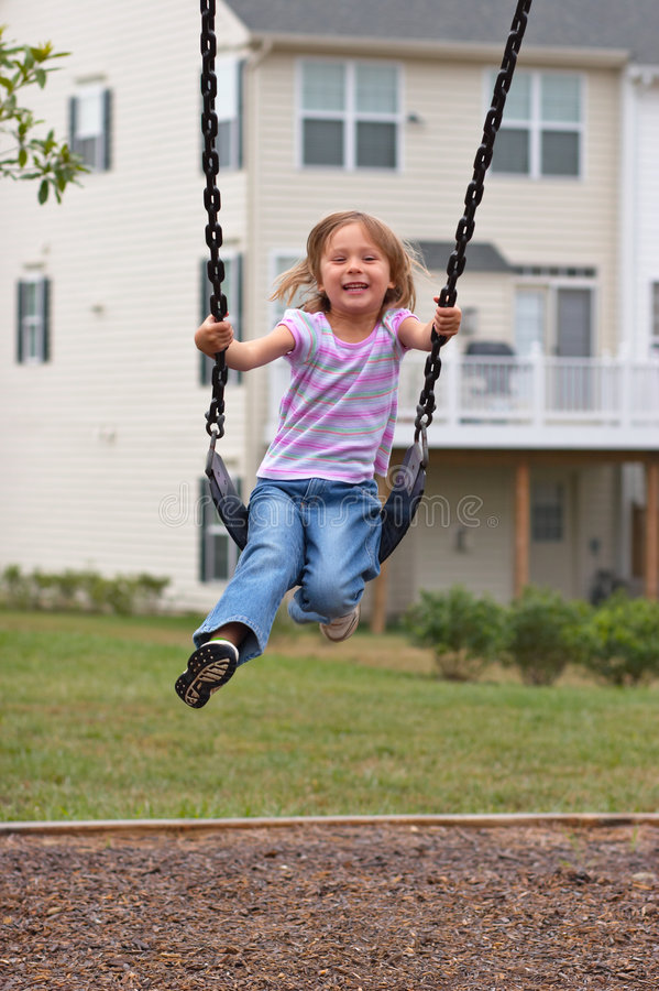 Klein meisje op speelplaatsschommeling stock foto
