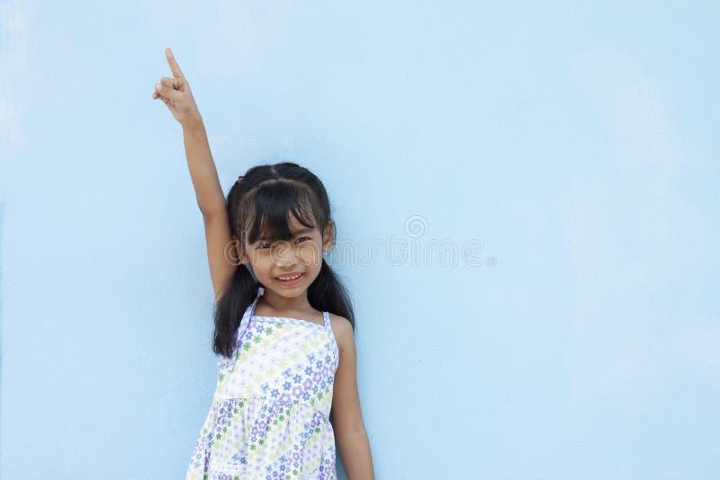 Klein meisje toont arm en wijsvinger op blauwe wand achtergrond stock foto's