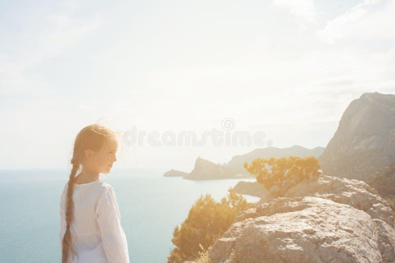 Klein meisjesverblijf op de bovenkant van berg stock afbeelding