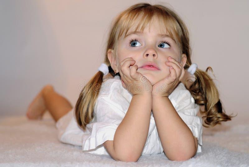 Klein mooi meisje in witte tanktop op bedden royalty-vrije stock foto