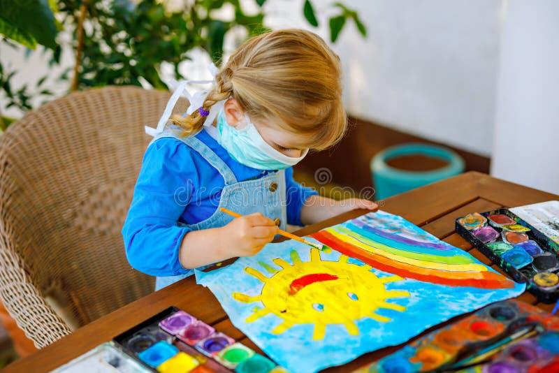Klein peutermeisje in een medisch masker, dat regenboog met waterkleuren schildert tijdens een pandemie van het coronavirus-quara stock afbeelding