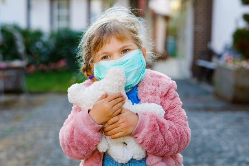 Klein peutermeisje in medisch masker als bescherming tegen pandemische coronavirus-quarantaineziekte Cute child gebruiken royalty-vrije stock foto's