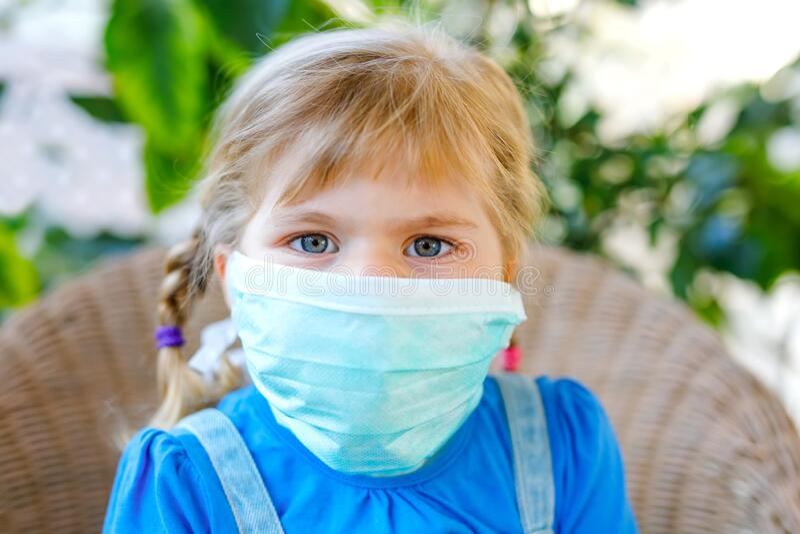 Klein peutermeisje in medisch masker als bescherming tegen pandemische coronavirus-quarantaineziekte Cute child gebruiken stock afbeelding