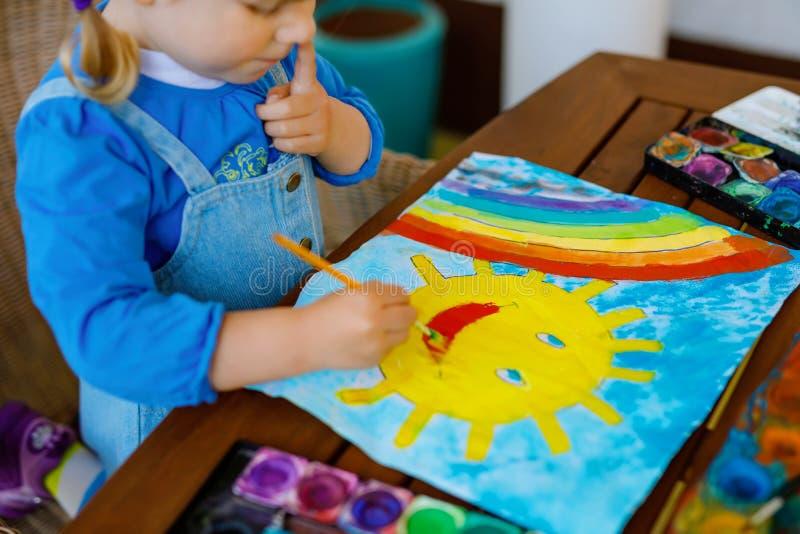Klein peutermeisje schildert regenboog en zon met waterkleuren tijdens een pandemische coronavirus-quarantaine-ziekte Kinderen stock afbeelding
