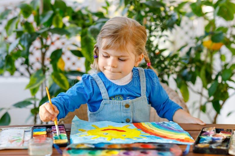 Klein peutermeisje schildert regenboog en zon met waterkleuren tijdens een pandemische coronavirus-quarantaine-ziekte Kinderen royalty-vrije stock foto