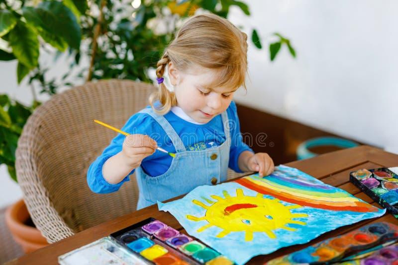 Klein peutermeisje schildert regenboog en zon met waterkleuren tijdens een pandemische coronavirus-quarantaine-ziekte Kinderen stock foto's