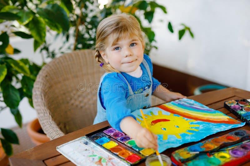 Klein peutermeisje schildert regenboog en zon met waterkleuren tijdens een pandemische coronavirus-quarantaine-ziekte Kinderen royalty-vrije stock afbeelding