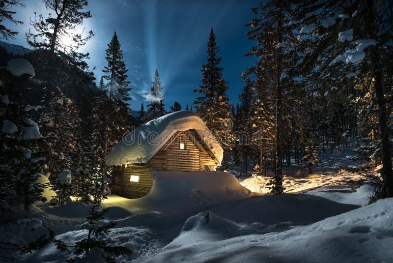 Klein plattelandshuisje in een mooi sneeuwbos bij maannacht stock afbeelding