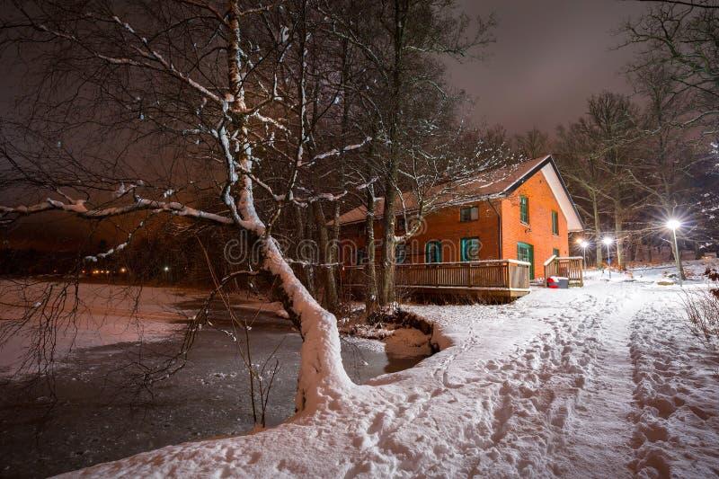 Klein plattelandshuisjehuis dichtbij meer bij sneeuwnacht royalty-vrije stock afbeeldingen