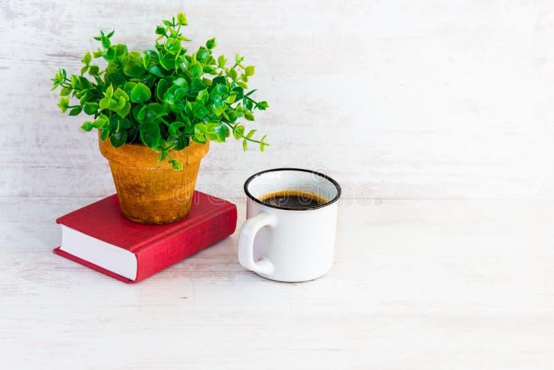 Klein rood boek, koffiekop en groene bloem in rustieke ceramische pot Witte houten achtergrond, exemplaarruimte stock fotografie